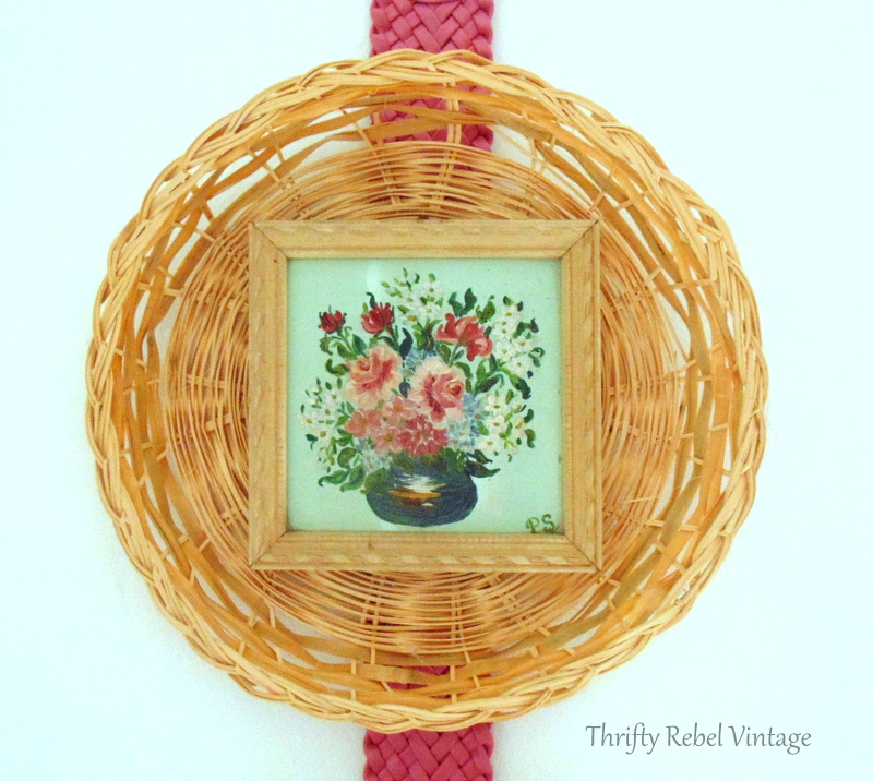 close up of small floral oil painting framed by a wicker plate