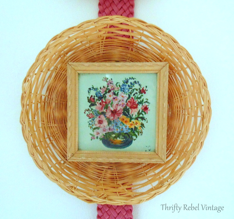 close up of small floral oil painting framed with a wicker plate