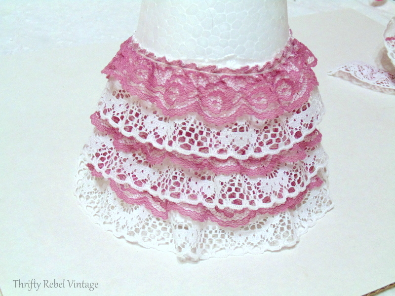 continuing to glue pink and white ribbon lace onto styrofoam cone