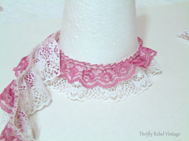 gluing ribbon lace around large styrofoam cone