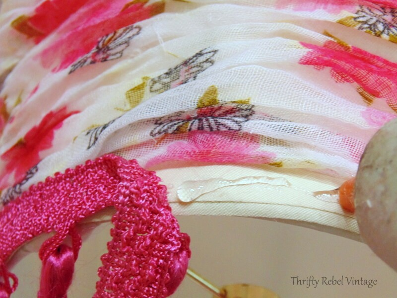 gluing tassel trim across the bottom and top of lampshade