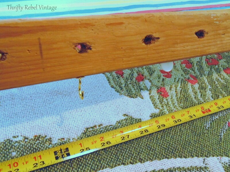 measuring and attaching brass hooks to wooden quilt frame piece for wall hanging 2