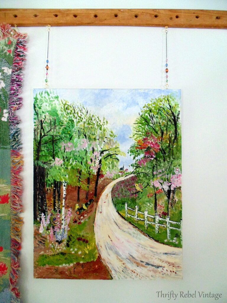 oil painting hung beside Monet water lily throw with brass hooks and pieces of vintage necklace