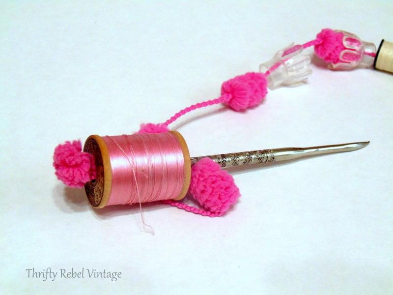 pushing pink puff ball yard through pink thread spool