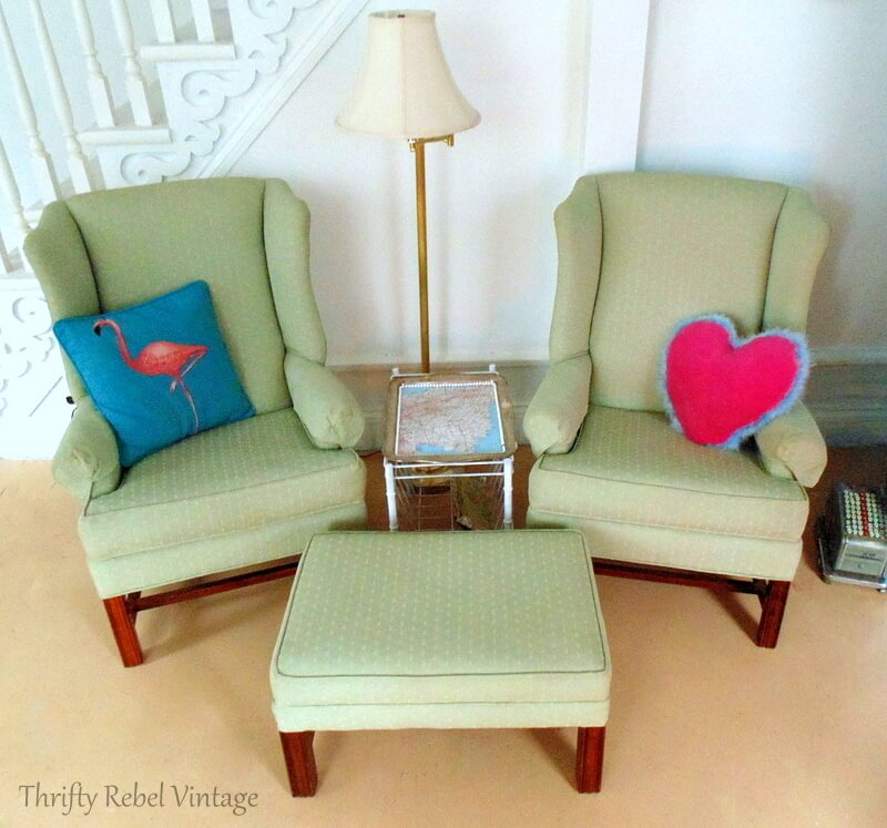 set of two green wing chairs with decorative pillows and matching ottomon before lampshade makeover
