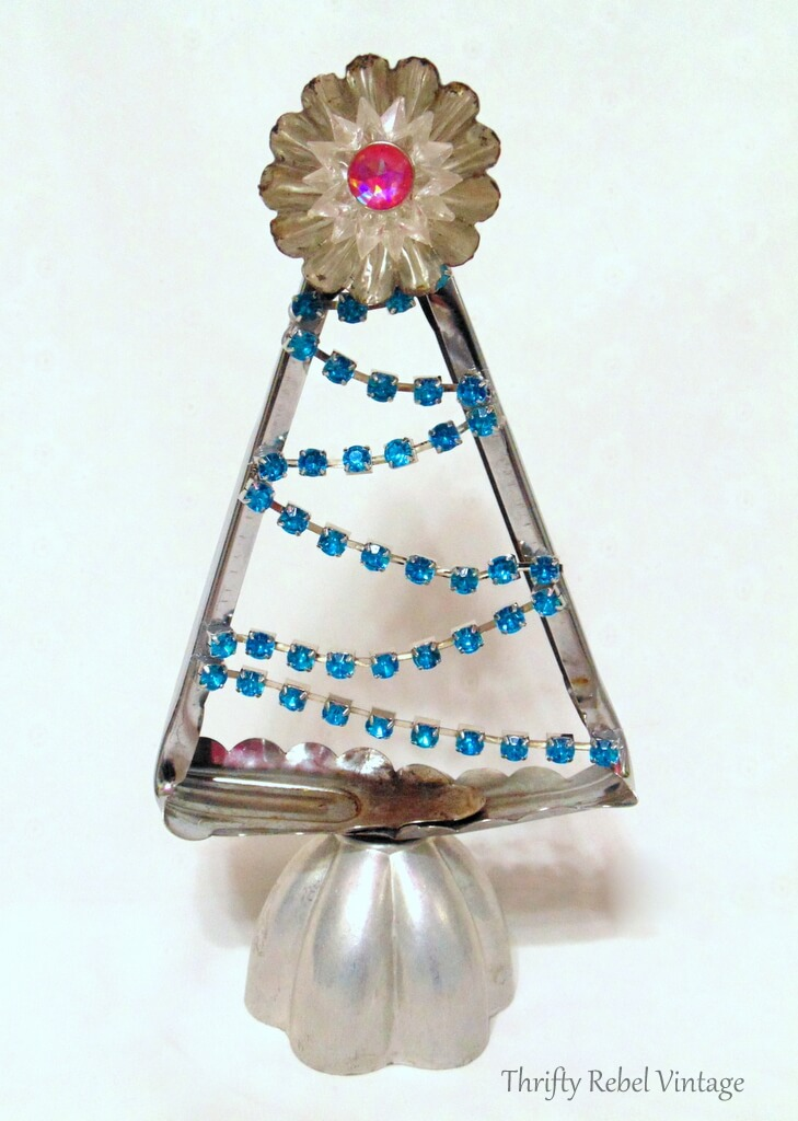 Repurposed salad tongs into Christmas tree with faux blue rhinestone bracelet, tart, tin, jello mold, and light reflector.