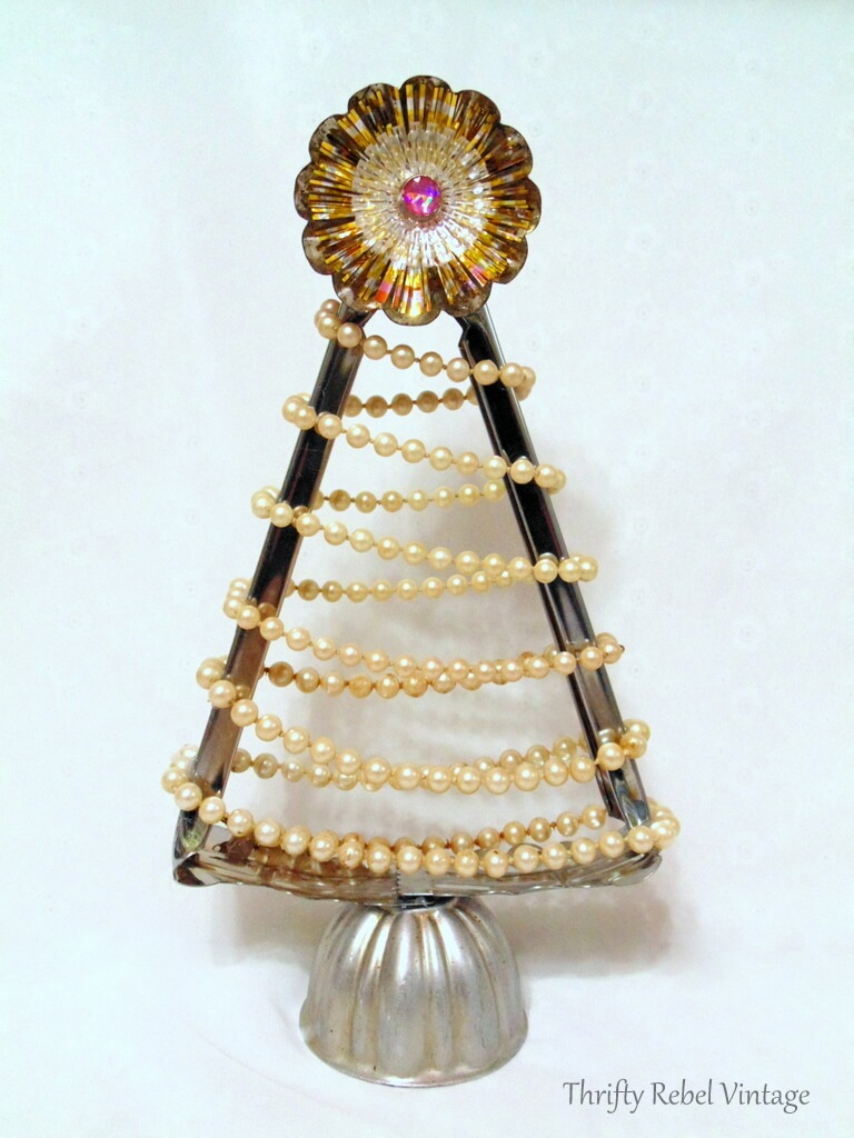 Repurposed salad tongs into Christmas tree with faux pearl necklace, tart, tin, jello mold, and light reflector