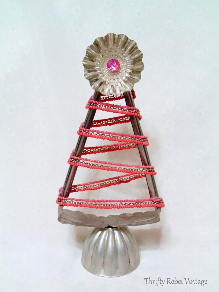 Repurposed salad tongs into Christmas tree with pink beaded necklace, tart, tin, jello mold, and light reflector.