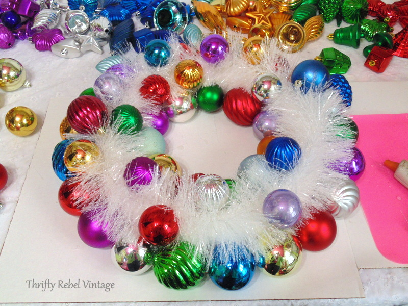 gluing Christmas ornaments onto wreath over sparkly white garland