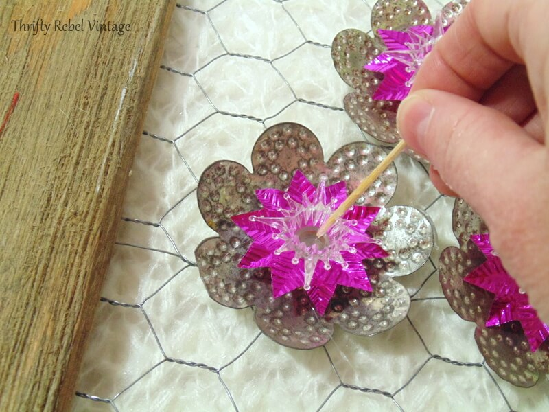 gluing faux pearls inside light reflectors for repurposed wall art project