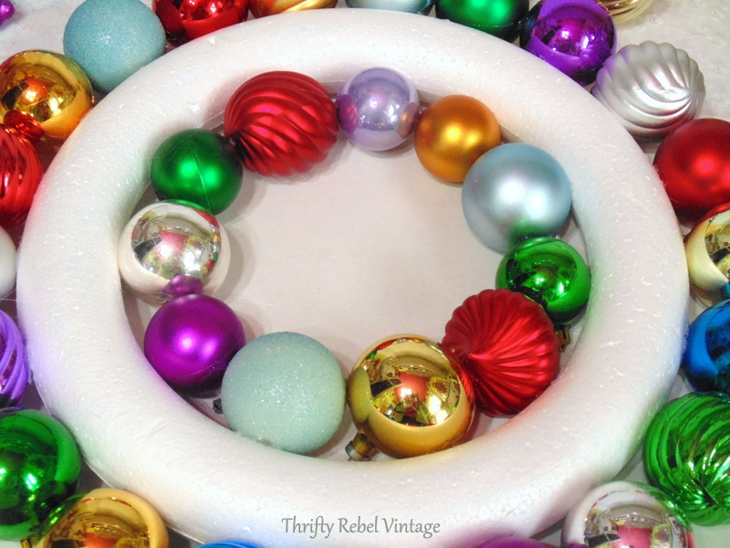 gluing plastic Christmas ornaments onto inside of wreath form