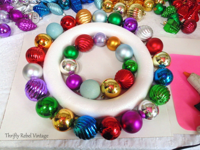 gluing plastic Christmas ornaments onto outisde of wreath form