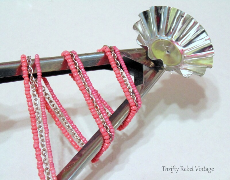 wrapping and gluing beaded necklace around salad tong for diy Christmas tree