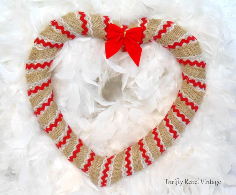 adding little red bow to burlap and red ric rac heart wreath