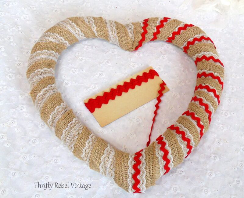 wrapping red ric rac trim around heart wreath form for winter Valentines's Day wreath