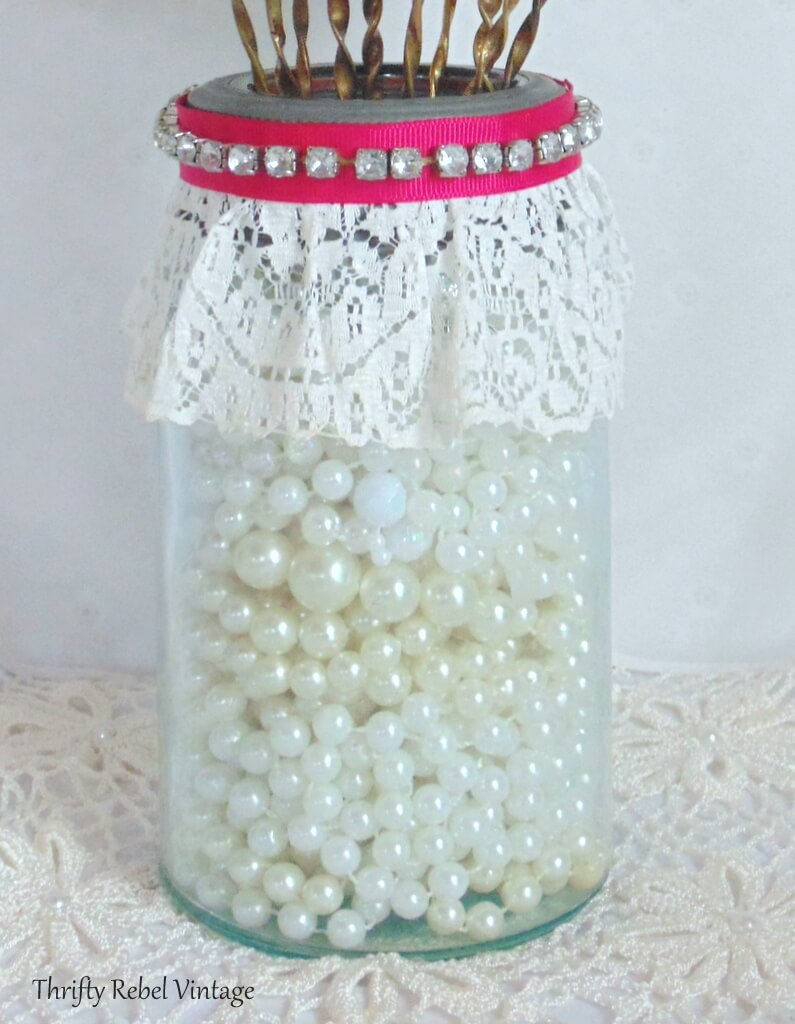 Blue glass Crown mason jar decorated with lace, pink ribbon, and rhinestone bracelet