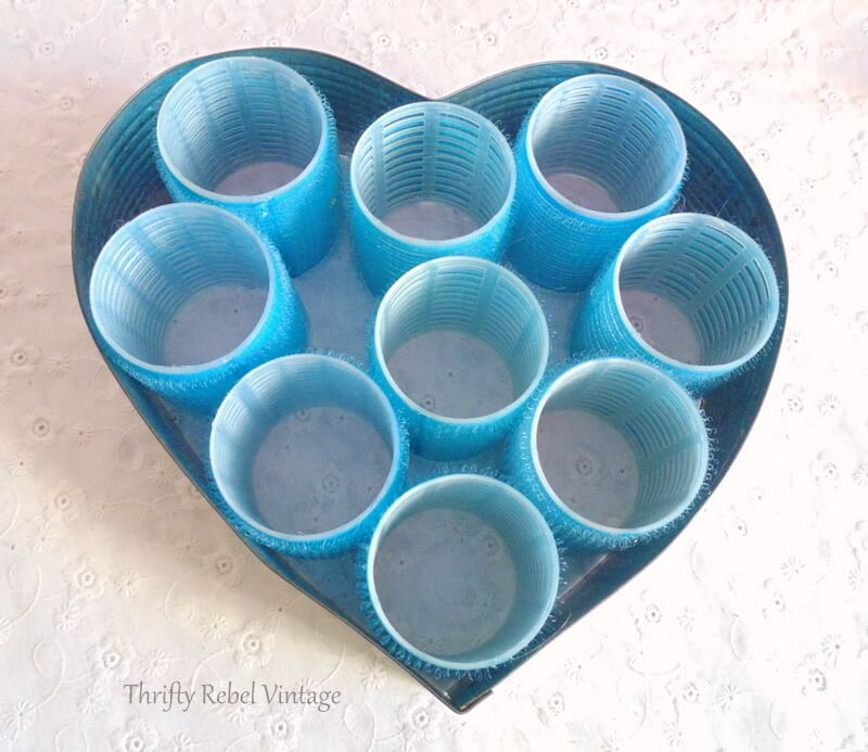 adding blue hair curlers inside vintage heart shaped cake frame for repurposed heart wreath