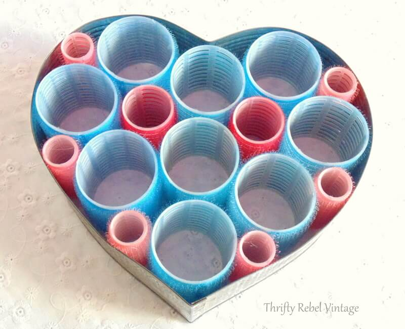 adding pink and red small hair curlers to fill spaces of repurposed heart wreath