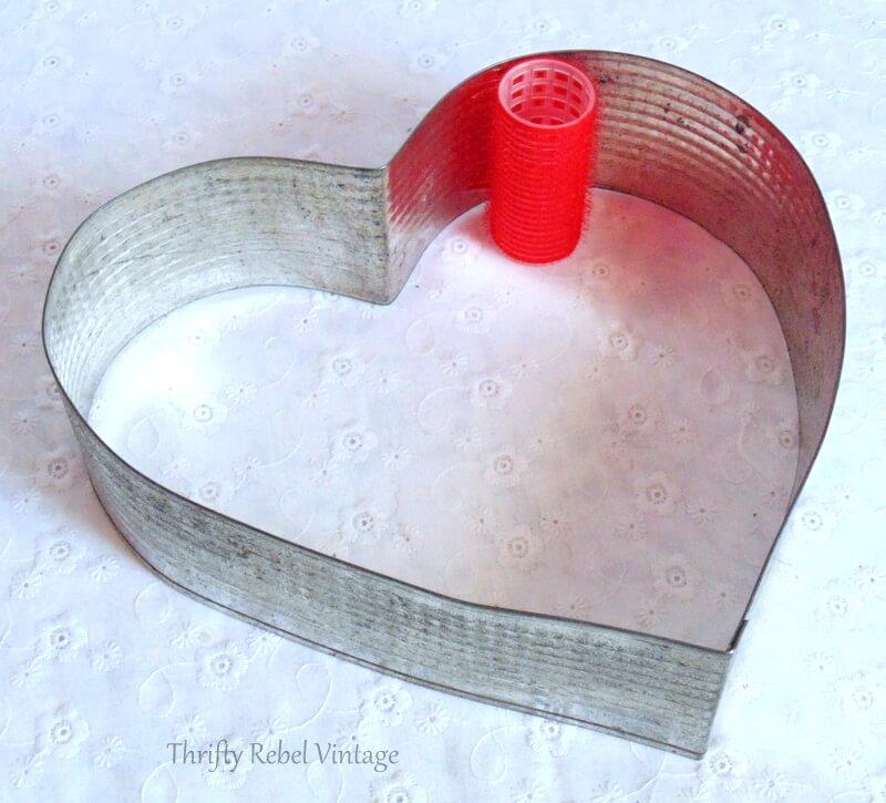 checking curler size inside vintage heart shaped cake frame