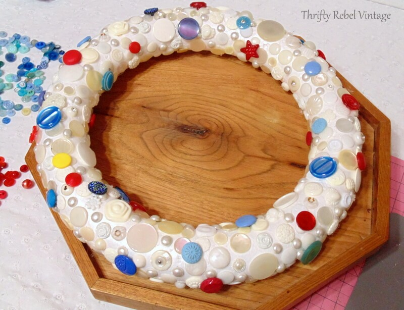 gluing blue buttons onto wreath form in the spaces between the white and cream buttons