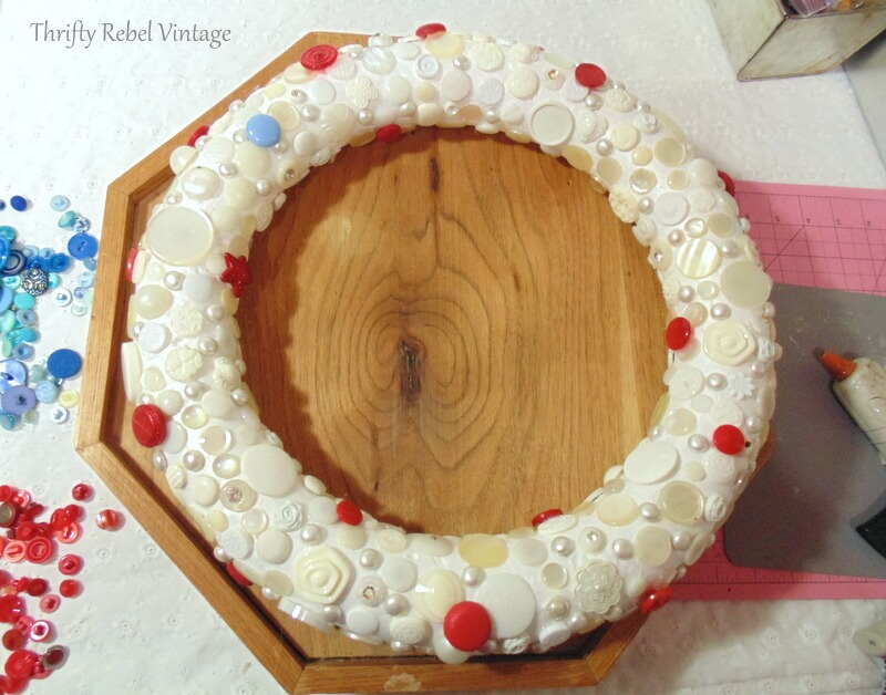 gluing red buttons onto wreath form in the spaces between the white and cream buttons