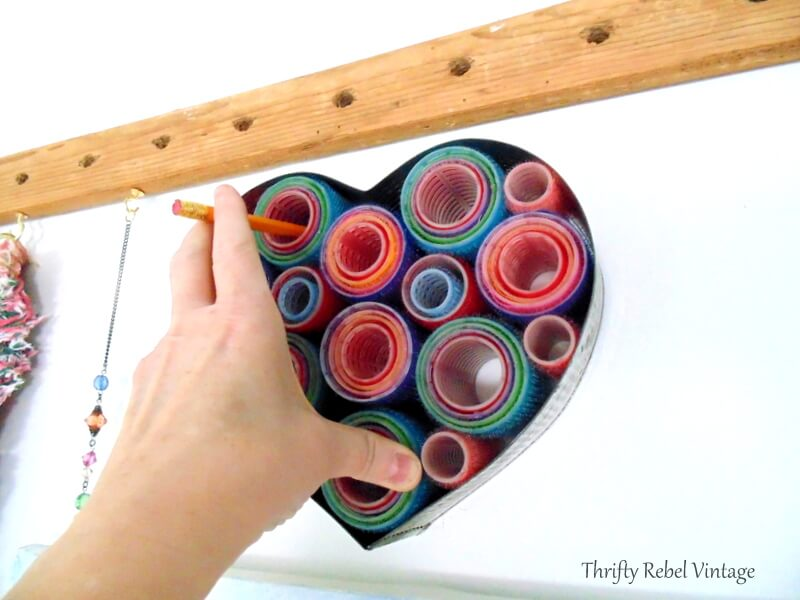 marking holes with pencil to hang repurposed hair curlers heart wreath