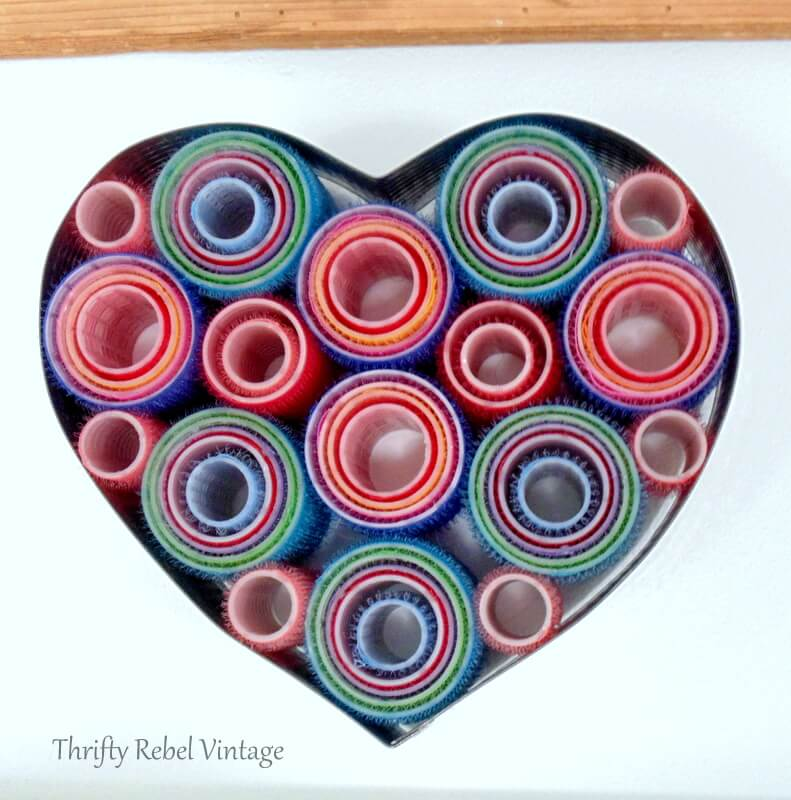 repurposed hair curlers and heart shaped cake frame wreath hanging on wall