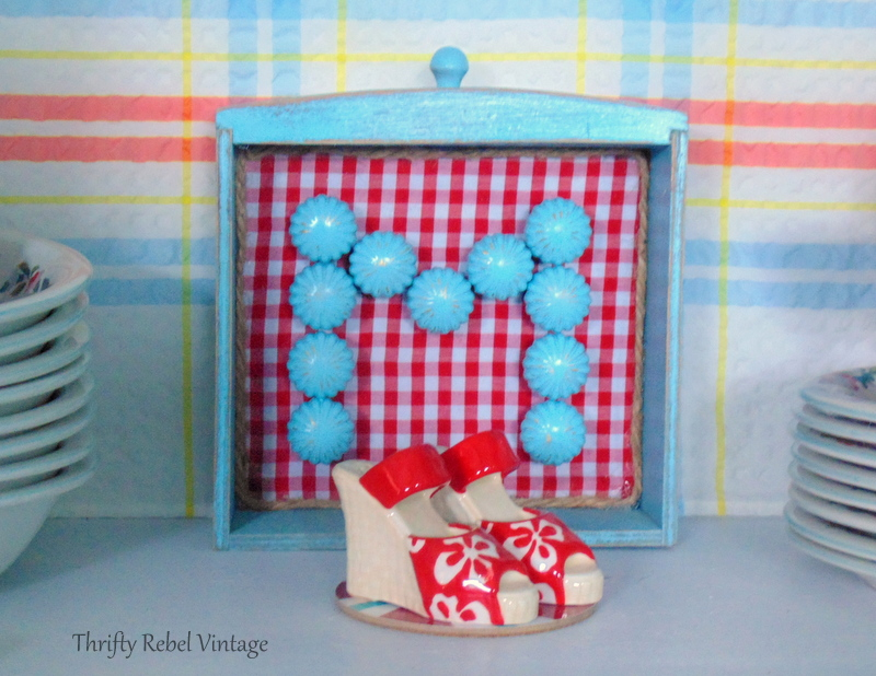 Repurposed drawer monogram sign using spray painted brass knobs and red and white checked fabric 1
