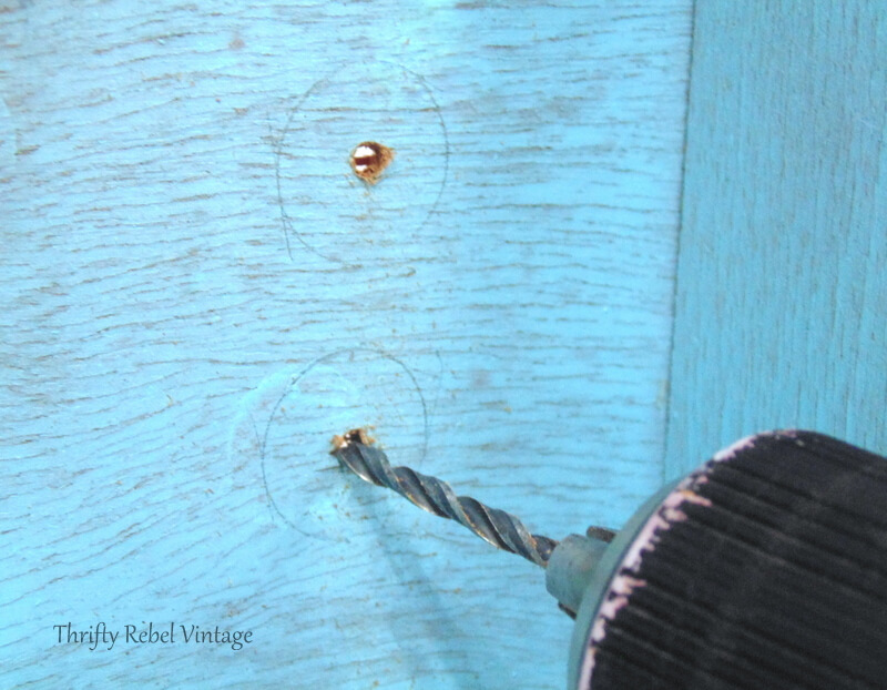 drilling holes in middle of pencil outline of drawer knobs