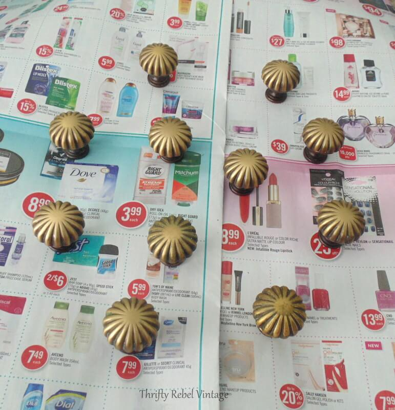 spreading out heavy brass drawer knobs on newspaper covered last susan to spray paint