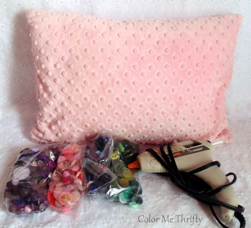 Pillow and buttons and hot glue gun for pillow makeover