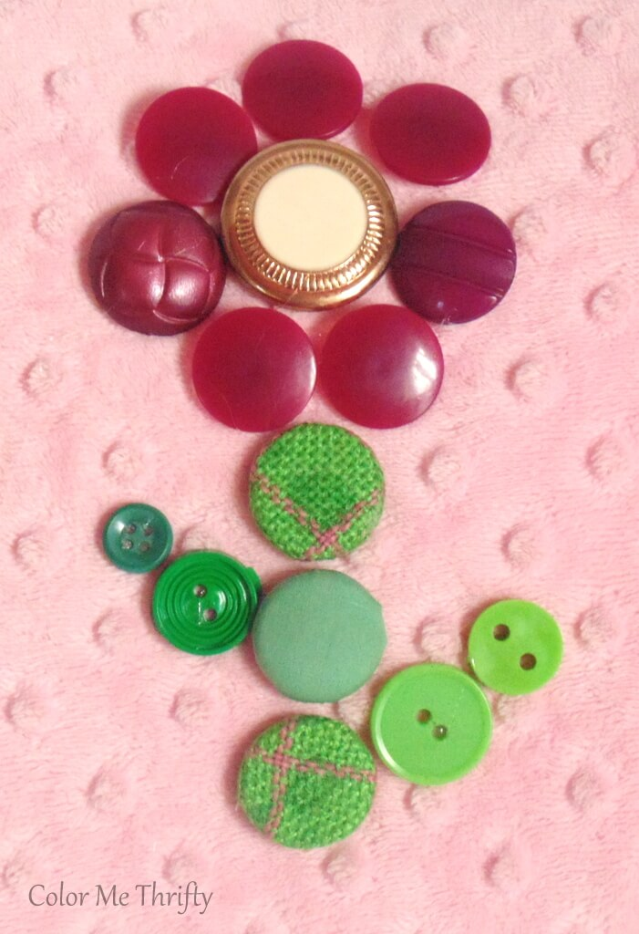 burgundy button flower with gold and faux pearl center and green button stem and leaves glued onto pink pillow