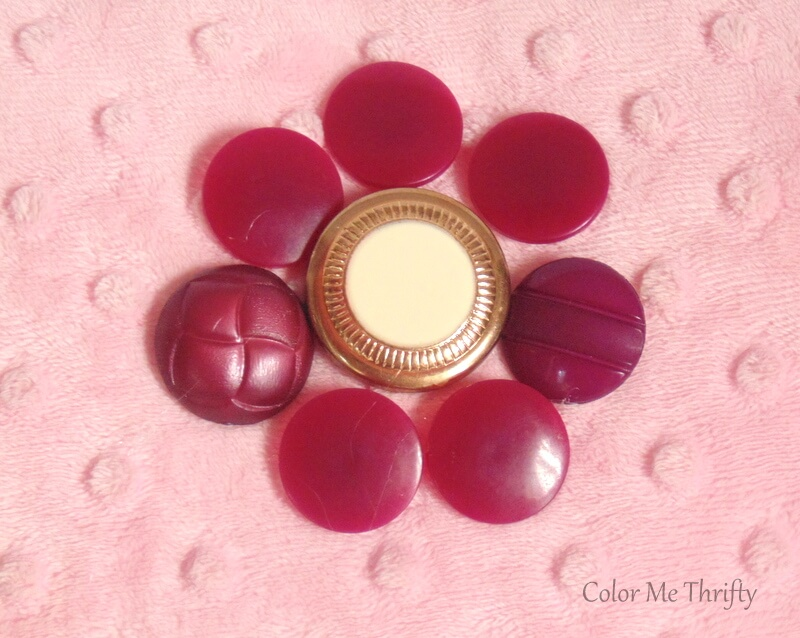 burgundy button flower with gold and faux pearl center glued onto pink pillow
