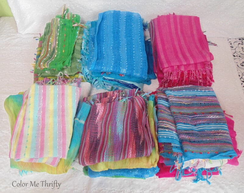 piles of ironed scarves ready for repurposing into no sew scarf curtains