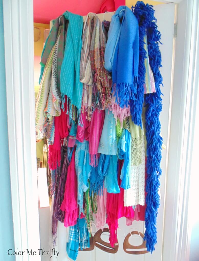 collection of thrifted scarves being stored on craft room door