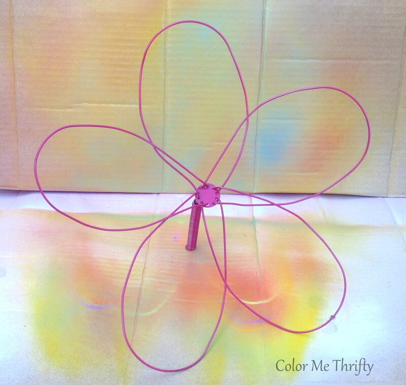 spray painting metal whisk flower in cardboard box