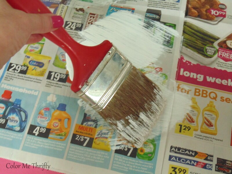 brushing off white paint onto newspaper to create dry brush
