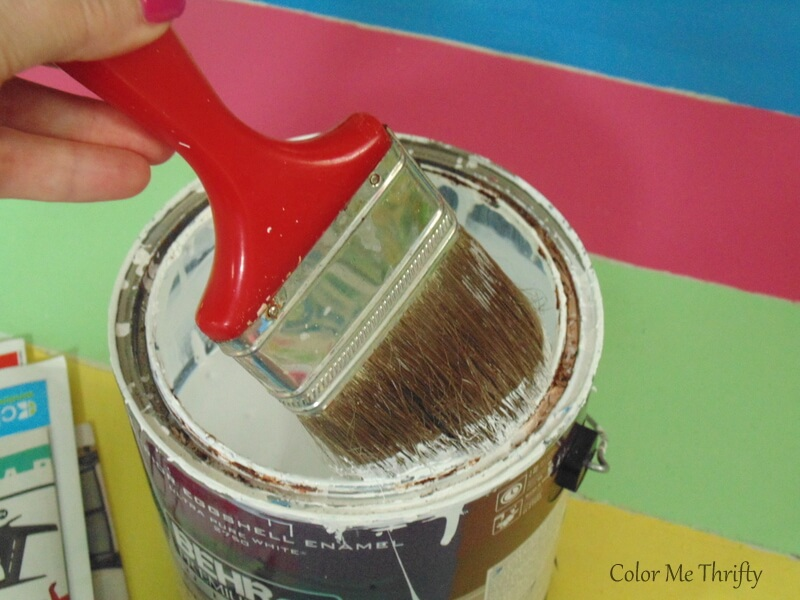 dipping brush into white paint for dry brushng wooden floor