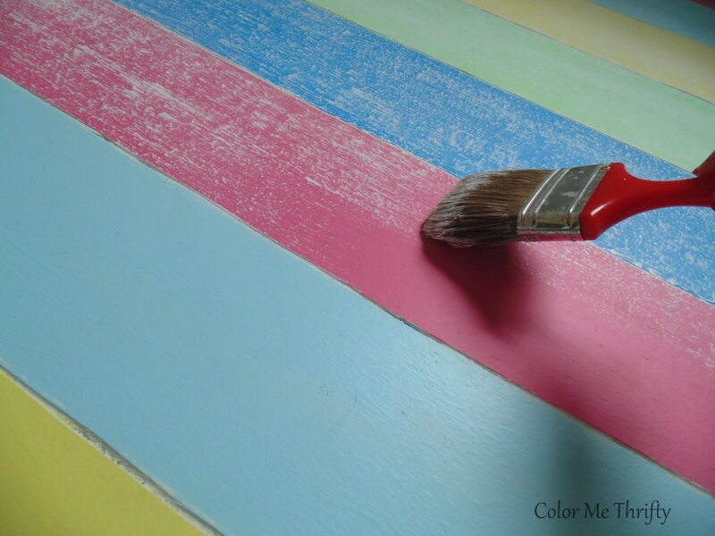 dry brushing white paint over pink painted stripe on living room floor