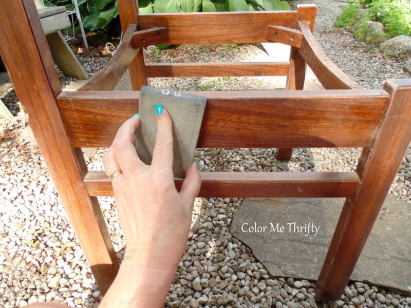 giving wooden chair a light sanding with a sanding block 3
