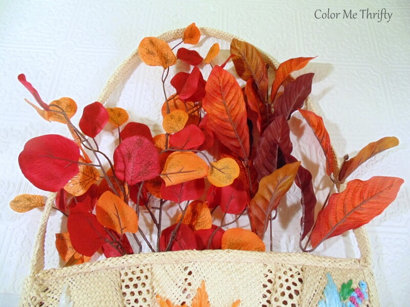 adding fall leaves for background of straw purse door decor
