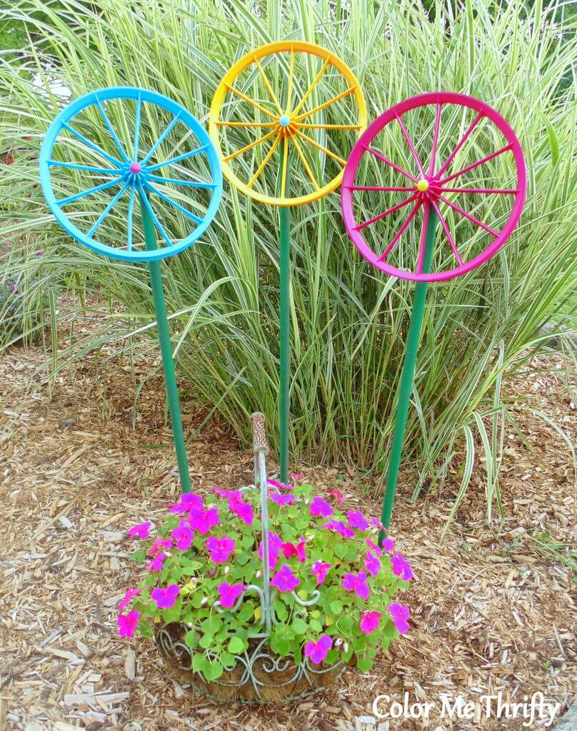 spray painted repurposed wheel flowers in garden