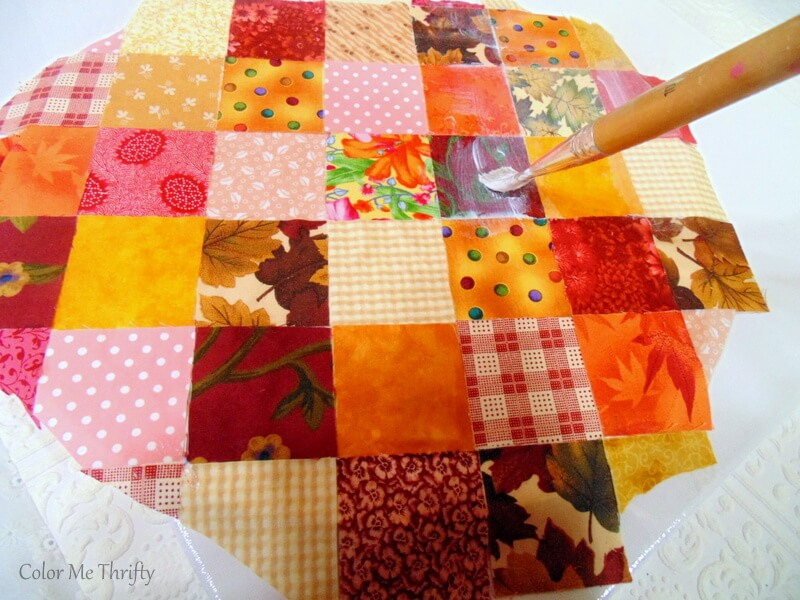applying top coat of fabric decoupage medium onto fabric quilt blocks