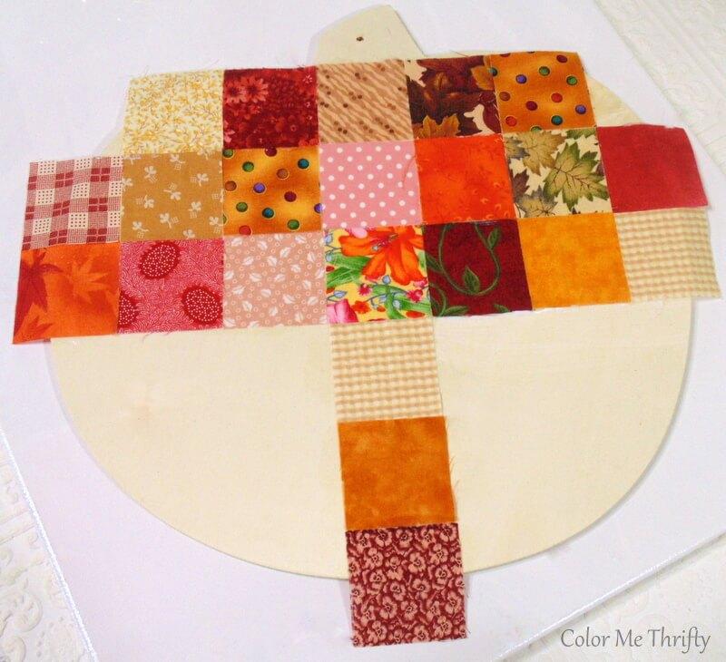 gluing fabric quilt blocks onto wooden pumpkin in a fun pattern