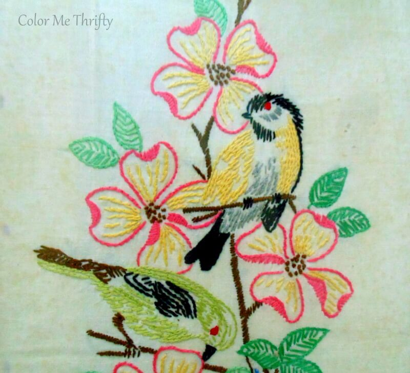 Close up of yellow and green needlework birds with pink flowers