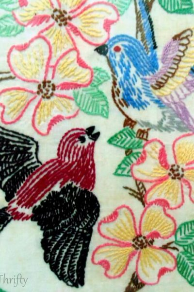 close up of blue and burgundy birds with pink flowers needlepoint