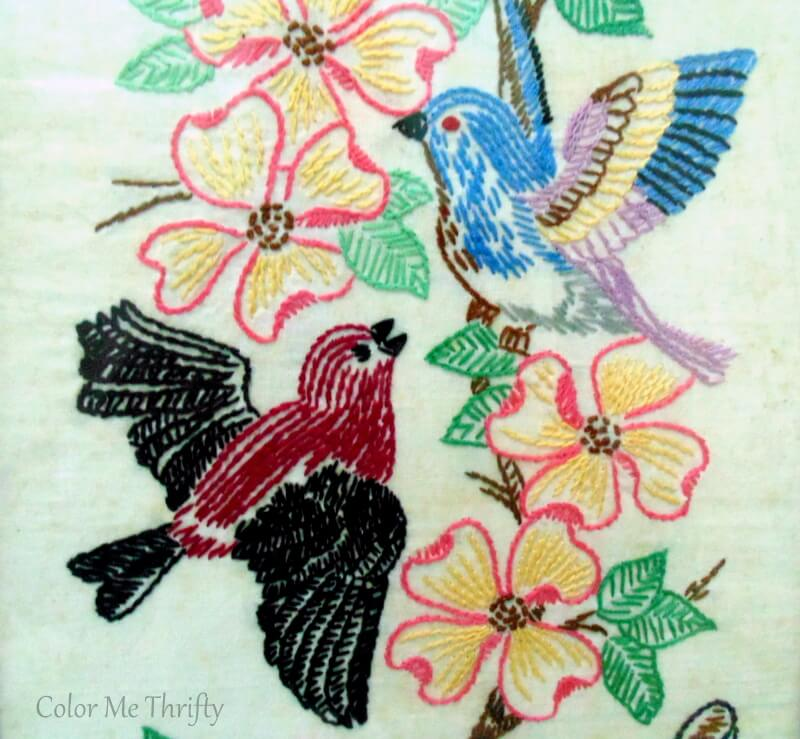 close up of blue and burgundy birds with pink flowers needlework