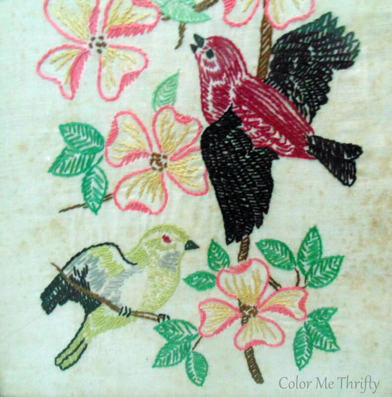 close up of burgundy and green birds with pink flowers needlework