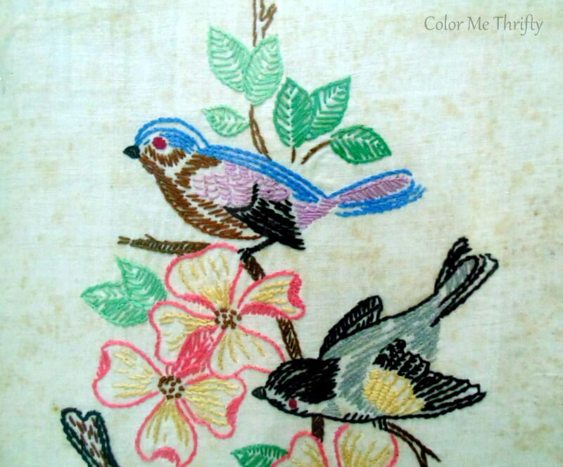 close up of colorful birds and pink flowers needlework