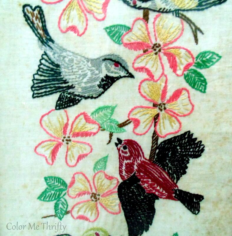 close up of grey and burgundy birds and pink flowers needlework